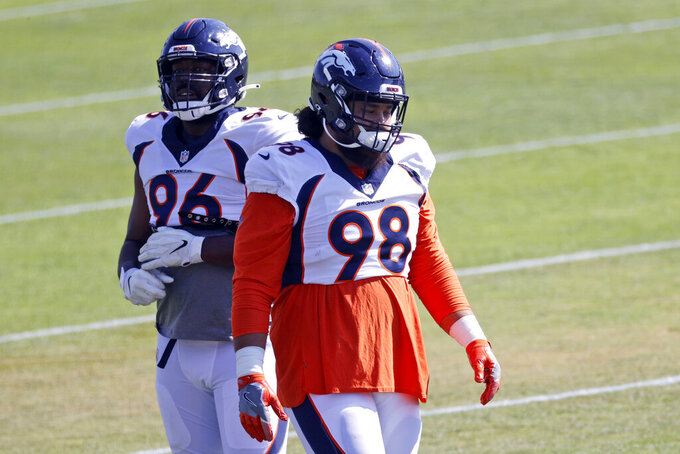 Denver Broncos nose tackle Mike Purcell, front, and defensive end Shelby Harris take part in drills during NFL football training camp Tuesday, Aug. 18, 2020, at the team's headquarters in Englewood, Colo. (AP Photo/David Zalubowski)