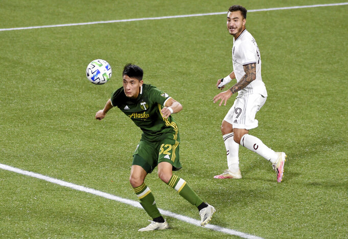 Portland Timbers defender Marco Farfan, left, heads the ball away from in front of the goal as Colorado Rapids forward Andre Shinyashiki looks on during the first half of an MLS soccer match in Portland, Ore., Wednesday, Nov. 4, 2020. (AP Photo/Steve Dykes)