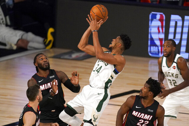 FILE - Miami Heat's Goran Dragic, bottom left, Jae Crowder, top left, and Jimmy Butler (22) defend as Milwaukee Bucks' Giannis Antetokounmpo (34) shoots during the first half of an NBA basketball conference semifinal playoff game inin Lake Buena Vista, Fla., in this Monday, Aug. 31, 2020, file photo. Bucks Khris Middleton, right rear, looks on. Having the NBA's best regular-season record and the league's MVP each of the last two years hasn't paid off for the Bucks in the playoffs. They're hoping an offseason overhaul of their roster will help them earn the title that has eluded this franchise since 1971 and make sure two-time reigning MVP Giannis Antetokounmpo stays in Milwaukee for years to come.(AP Photo/Mark J. Terrill, File)