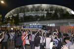 People gather outside the National Stadium to send off a bus carrying Olympic participants after the closing ceremony of the Tokyo Olympics in Tokyo on Aug. 8, 2021. The Tokyo Olympics are over, but it's still vacation season in Japan, and many are ignoring government pleas to avoid travel and stay away from bars and restaurants even as the coronavirus spikes at record levels. (Kyodo News via AP)