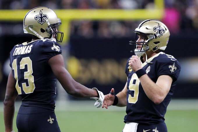 New Orleans Saints quarterback Drew Brees (9) greets New Orleans Saints wide receiver Michael Thomas (13) after a touchdown in the second half of an NFL football game against the Arizona Cardinals in New Orleans, Sunday, Oct. 27, 2019. (AP Photo/Bill Feig)