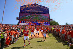 FILE- In this Sept. 7, 2013, file photo, Clemson players run down the hill before the start of an NCAA college football game against South Carolina State at Memorial Stadium in Clemson, S.C. Clemson is moving forward with plans to host its scheduled football game on Saturday while Hurricane Florence wreaks havoc on the Carolinas' coastline with officials bracing for historic flooding and record-setting rainfall that has forced people to evacuate their homes to escape the wrath of the storm. (AP Photo/Richard Shiro, File)