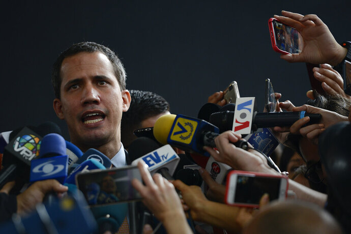 Opposition leader Juan Guaido speaks to the press at a theater in the El Hatillo neighborhood where opposition lawmakers are holding a session after their vehicles were attacked by government supporters while driving to the National Assembly in downtown Caracas, Venezuela, Wednesday, Jan. 15, 2020. It's the second time this month that lawmakers have been barred from from the building that houses the only branch of government out of control of President Nicolas Maduro's government. (AP Photo/Matias Delacroix)