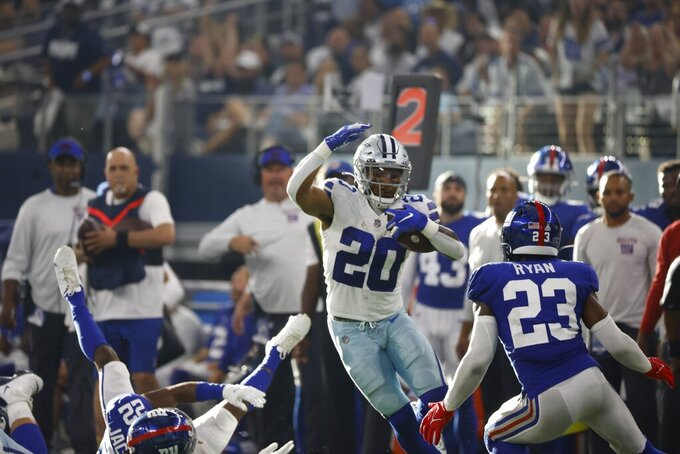 Dallas Cowboys running back Tony Pollard (20) runs the ball for a first down as New York Giants cornerback Logan Ryan (23) defends in the second half of an NFL football game in Arlington, Texas, Sunday, Oct. 10, 2021. (AP Photo/Ron Jenkins)