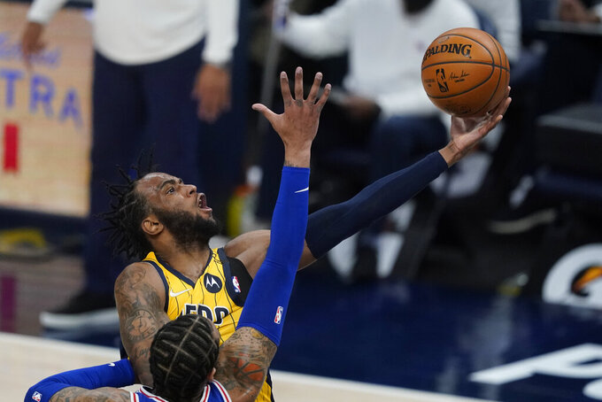 Indiana Pacers' Oshae Brissett (12) puts up a shot against Philadelphia 76ers' Mike Scott during the second half of an NBA basketball game, Tuesday, May 11, 2021, in Indianapolis. (AP Photo/Darron Cummings)