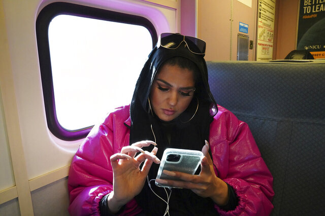 In this Dec. 20, 2019, photo, Amani Al-Khatahtbeh, founder of MuslimGirl.com, sits for an interview inside her family's video game and electronic store business in Somerville, N.J. Al-Khatahtbeh started the website as a way to defy Muslim stereotypes after 9/11. A decade later, Al-Khatahtbeh has built it into an online magazine with a global audience. (AP Photo/Emily Leshner)