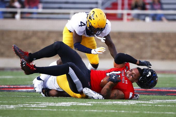 West Virginia's Josh Chandler-Semedo (7) and Alonzo Addae (4) tackle Texas Tech's Travis Koontz (15) during the second half of an NCAA college football game on Saturday, Oct. 24, 2020, in Lubbock, Texas. (AP Photo/Brad Tollefson)