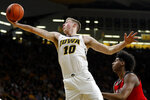 Iowa guard Joe Wieskamp (10) grabs a rebound over Rutgers center Myles Johnson, right, during the first half of an NCAA college basketball game, Saturday, March 2, 2019, in Iowa City, Iowa. (AP Photo/Charlie Neibergall)