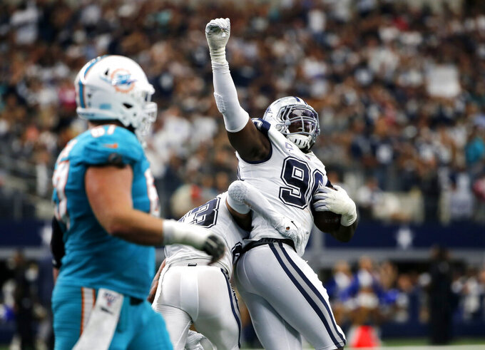 Dallas Cowboys defensive back Darian Thompson (23) and defensive end Demarcus Lawrence (90) celebrate after recovering a Miami Dolphins fumble in the first half of an NFL football game in Arlington, Texas, Sunday, Sept. 22, 2019. (AP Photo/Michael Ainsworth)
