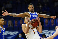 Loyola of Chicago guard Lucas Williamson (1) drives to the basket ahead of Drake forward Tremell Murphy, rear, during the first half of an NCAA college basketball game, Sunday, Feb. 14, 2021, in Des Moines, Iowa. (AP Photo/Charlie Neibergall)