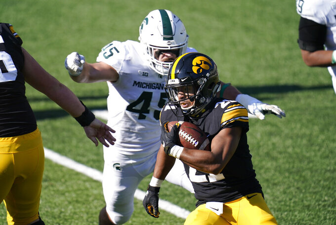 Iowa running back Ivory Kelly-Martin runs from Michigan State linebacker Noah Harvey, rear, during the first half of an NCAA college football game, Saturday, Nov. 7, 2020, in Iowa City, Iowa. (AP Photo/Charlie Neibergall)