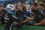 Mercedes driver Valtteri Bottas of Finland is congratulated by team staff after after he clocked the fastest time during the qualifying session at the Monza racetrack, in Monza, Italy , Friday, Sept.10, 2021. The Formula one race will be held on Sunday. (Lars Baron/Pool photo via AP)