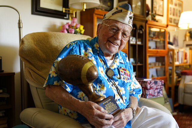 Mickey Ganitch, a 101-year-old survivor of the attack on Pearl Harbor, holds a football statue he was given, in the living room of his home in San Leandro, Calif., Nov. 20, 2020. Ganitch was getting ready for a match pitting his ship, the USS Pennsylvania, against the USS Arizona when Japanese planes bombed Pearl Harbor on Dec. 7, 1941. The game never happened. Instead, Ganitch spent the morning, still in his football uniform, looking out for attacking planes that anti-aircraft gunners could shoot down. (AP Photo/Eric Risberg)