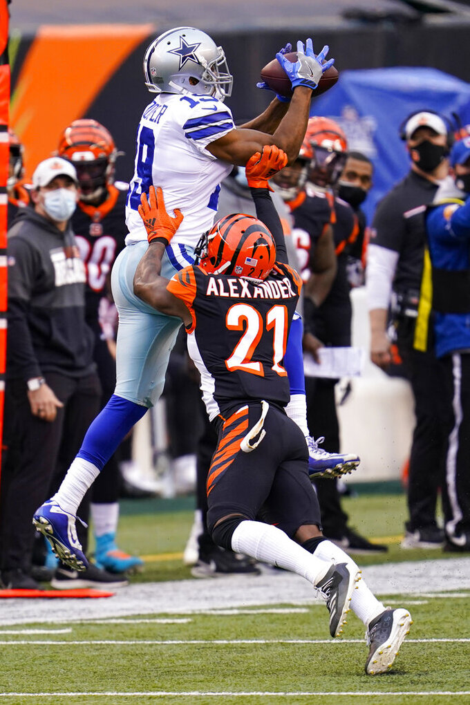 Dallas Cowboys wide receiver Amari Cooper (19) makes a catch over Cincinnati Bengals cornerback Mackensie Alexander (21) in the first half of an NFL football game in Cincinnati, Sunday, Dec. 13, 2020. (AP Photo/Bryan Woolston)