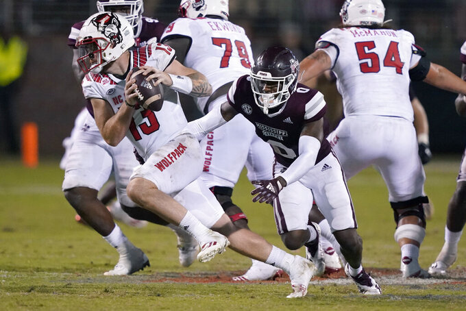 North Carolina State quarterback Devin Leary (13) is pursued by Mississippi State safety Jalen Green (0) during the second half of an NCAA college football game in Starkville, Miss., Saturday, Sept. 11, 2021. (AP Photo/Rogelio V. Solis)