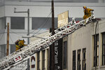 Los Angeles Fire Department firefighters work the scene of a structure fire that injured multiple firefighters, according to a fire department spokesman, Saturday, May 16, 2020, in Los Angeles. (AP Photo/Mark J. Terrill)