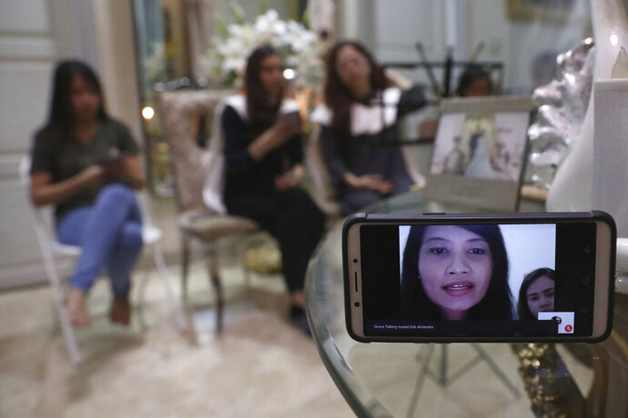 A relative of Dr. Michael Robert Marampe is seen through a mobile phone screen as she attends an online memorial service to mark the 40th day since Marampe passed away due to COVID-19 in Jakarta, Indonesia, on June 5, 2020. Marampe knew what he wanted to be since he was a kid: a doctor and a pianist. He became both, and his passion for music even led him to Tri Novia Septiani - a woman he never got to marry because he got the coronavirus. Marampe became one of dozens of doctors the coronavirus has claimed so far in Indonesia. (AP Photo/Tatan Syuflana)