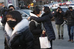 A student hugs her mother, right, before entering a high school to take the college entrance exam in Seoul, South Korea, Thursday, Dec. 3, 2020. South Korean officials urged on Wednesday people to remain at home if possible and cancel gatherings as about half a million students prepare for the crucial national college exam. (AP Photo/Ahn Young-joon)