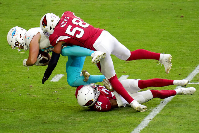 Miami Dolphins tight end Durham Smythe his tackled by Arizona Cardinals middle linebacker Jordan Hicks (58) and free safety Jalen Thompson (34) during the first half of an NFL football game, Sunday, Nov. 8, 2020, in Glendale, Ariz. (AP Photo/Ross D. Franklin)