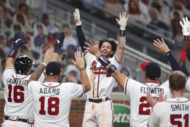 Atlanta Braves' Dansby Swanson, center, is greeted by teammates rushing the field at home after his two-run, game ending home run in the ninth inning of the team's baseball game against the Washington Nationals on Monday, Aug. 17, 2020, in Atlanta. (Curtis ComptonAtlanta Journal-Constitution via AP)