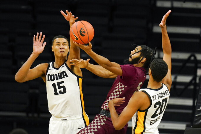 North Carolina Central forward Nehemie Kabeya, center, drives to the basket between Iowa's Keegan Murray (15) and Kris Murray (20) during the second half of an NCAA college basketball game, Wednesday, Nov. 25, 2020, in Iowa City, Iowa. Iowa won 97-67. (AP Photo/Charlie Neibergall)