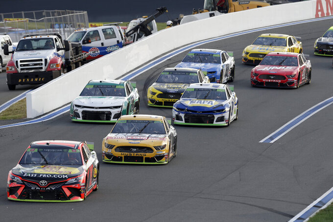 Drivers navigate Turn 2 during the NASCAR Cup Series auto race at Charlotte Motor Speedway in Concord, N.C., Sunday, Sept. 29, 2019. (AP Photo/Gerry Broome)