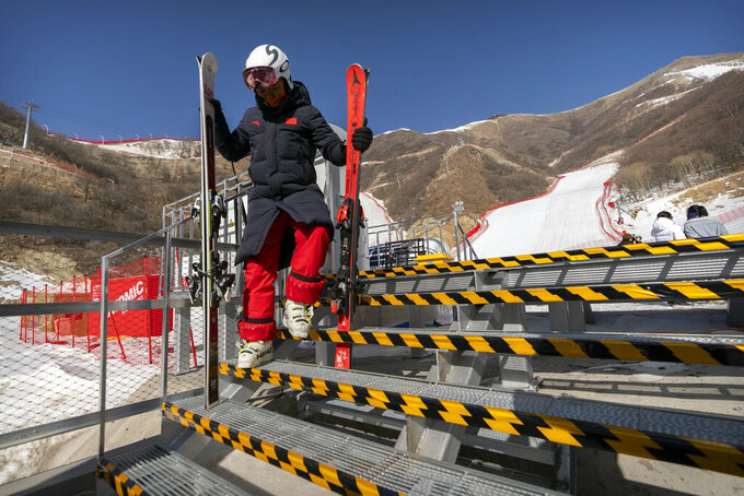 A skier navigates a flight of stairs as he carries his equipment at the National Alpine Skiing Center in Yanqing on the outskirts of Beijing, Friday, Feb. 5, 2021. Beijing Olympic organizers showed off the downhill skiing venue and the world's longest bobsled and luge track Friday, one year ahead of the scheduled opening of the 2022 Olympic Winter Games. (AP Photo/Mark Schiefelbein)