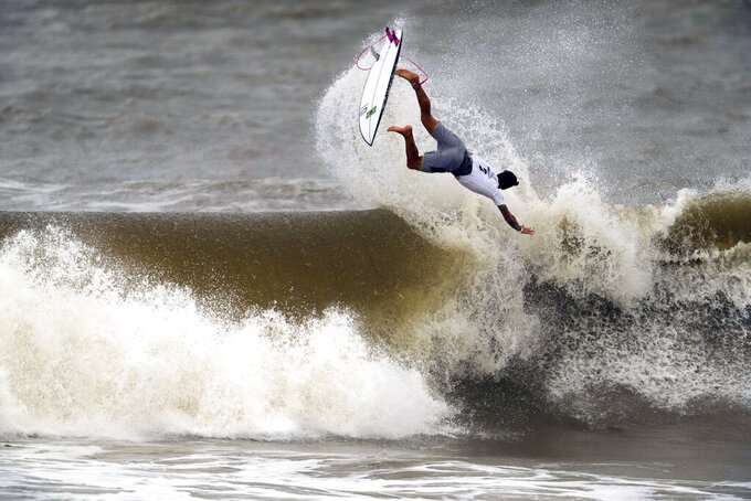 Brazil's Gabriel Medina goes to the air on a wave during the semifinals of the men's surfing competition at the 2020 Summer Olympics, Tuesday, July 27, 2021, at Tsurigasaki beach in Ichinomiya, Japan. (AP Photo/Francisco Seco)