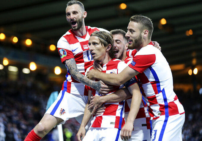 Croatia's Luka Modric is celebrated after scoring his side's second goal during the Euro 2020 soccer championship group D match between Croatia and Scotland at the Hampden Park Stadium in Glasgow, Tuesday, June 22, 2021.(Robert Perry/Pool via AP))