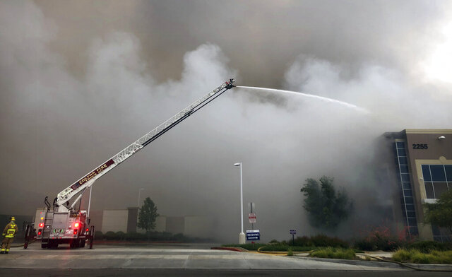 Firefighters from multiple agencies battle a warehouse fire in Redlands, Calif., on Friday, June 5, 2020. The destroyed a huge commercial building, about 60 miles east of Los Angeles,  but there are no reports of injuries. (Watchara Phomicinda/The Orange County Register via AP)