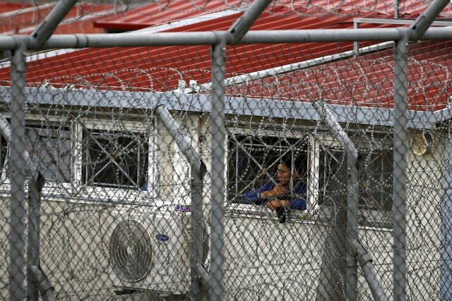 FILE - In this file photo dated Sunday, March 8, 2020, a migrant looks out from a detention center in the village of Fylakio, Evros region, near the Greek-Turkish border.  Police in northern Greece say migrants staged a violent protest at the Fylakio holding site near the country's border with Turkey, Tuesday May 12, 2020, causing extensive damage to living quarters and facilities.  (AP Photo/Giannis Papanikos, FILE)