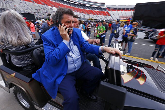 Mike Helton, NASCAR vice-chairman, rides through the pit area before a NASCAR Cup Series auto race, Sunday, April 7, 2019, in Bristol, Tenn. (AP Photo/Wade Payne)