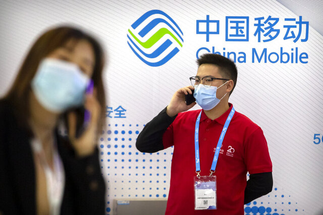FILE - In this Oct. 14, 2020, file photo, people wearing face masks to protect against the spread of the coronavirus talk on their cellphones near a booth for Chinese telecommunications firm China Mobile at the PT Expo in Beijing. The New York Stock Exchange says it is withdrawing plans to remove shares of three Chinese state-owned phone carriers under an order by President Donald Trump.(AP Photo/Mark Schiefelbein, File)