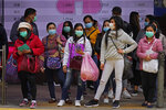 People wear protective face masks on a street corner in Hong Kong, Sunday, Feb. 9, 2020. China's death toll from the new virus outbreak has risen to over 800, surpassing the number of fatalities in the 2002-03 SARS epidemic, as other governments stepped up efforts to block the disease. (AP Photo/Vincent Yu)