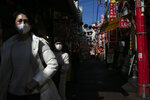 In this Feb. 13, 2020, photo, two women wearing masks tour Yokohama's Chinatown, near Tokyo. A top Olympic official made clear Friday the 2020 Games in Tokyo will not be cancelled despite the virus that has spread from China. (AP Photo/Jae C. Hong)