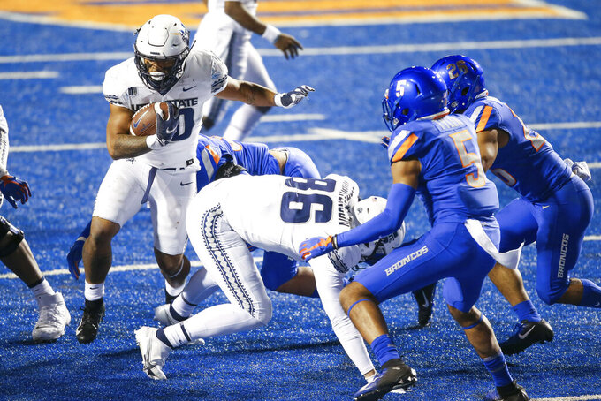 Utah State running back Jaylen Warren (20) runs around the block of Utah State tight end Bryce Mortenson (86) against the Boise State defense in the second half in an NCAA college football game Saturday, Oct. 24, 2020, in Boise, Idaho.Boise State won 42-13. (AP Photo/Steve Conner)