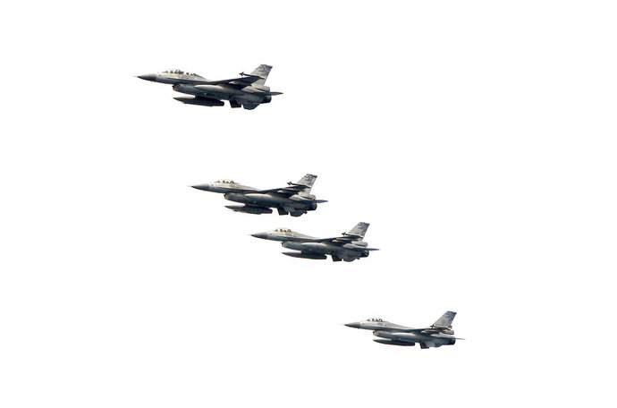 FILE - In this April 13, 2018, file photo, Taiwanese F-16 jet fighters fly in close formation during a navy exercise at Suao naval station in Yilan County, northeastern Taiwan. China demanded Tuesday, Sept. 25, 2018, that the U.S. cancel a $330 million sale of military equipment to Taiwan, warning of