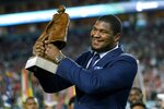 FILE - In this Sunday, Feb. 2, 2020, file photo, Jacksonville Jaguars' Calais Campbell raises the Walter Payton NFL Man of the Year trophy before the first half of the NFL Super Bowl 54 football game, in Miami Gardens, Fla. On Sunday, March 15, 2020, the Baltimore Ravens agreed to trade a fifth-round draft pick in the upcoming draft to the Jacksonville Jaguars for veteran defensive lineman Calais Campbell. (AP Photo/David J. Phillip, File)