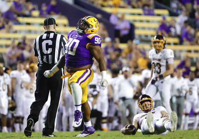 LSU defensive tackle Jacobian Guillory (90) celebrates after sacking Central Michigan quarterback Jacob Sirmon, bottom right, during the second half of an NCAA college football game in Baton Rouge, La,. Saturday, Sept. 18, 2021. (AP Photo/Derick Hingle)