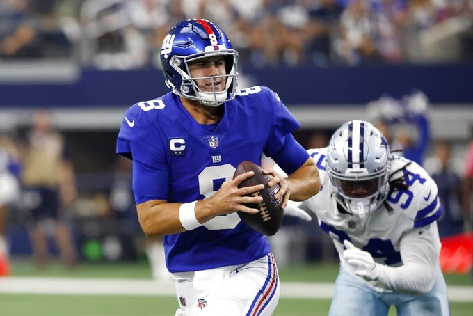 New York Giants quarterback Daniel Jones (8) scrambles out of the pocket under pressure from Dallas Cowboys defensive end Randy Gregory (94) in the first half of an NFL football game in Arlington, Texas, Sunday, Oct. 10, 2021. (AP Photo/Ron Jenkins)