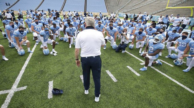 North Carolina coach Mack Brown meets with his team following their victory over Syracuse in an NCAA college football game Saturday, Sept. 12, 2020, in Chapel Hill, N.C. (Robert Willett/The News & Observer via AP, Pool)