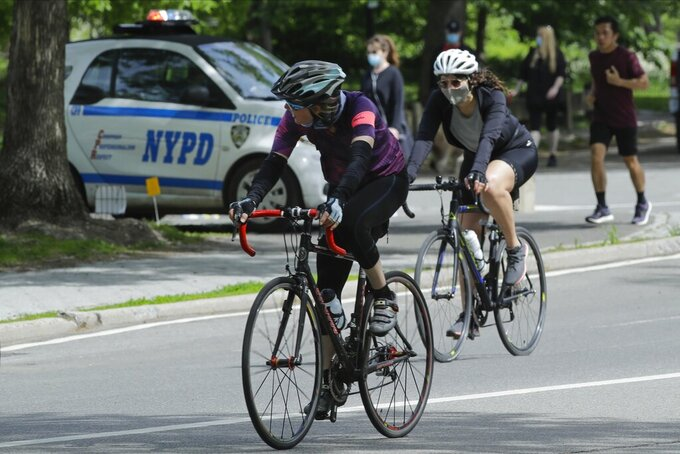 Cyclists wearing protective masks pass a New York Police vehicle near an entrance to Central Park during the coronavirus pandemic Saturday, May 16, 2020, in New York. (AP Photo/Frank Franklin II)