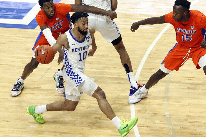 Kentucky's Davion Mintz (10) drives near Florida's Scottie Lewis (23) and Osayi Osifo (15) during the second half of an NCAA college basketball game in Lexington, Ky., Saturday, Feb. 27, 2021. (AP Photo/James Crisp)
