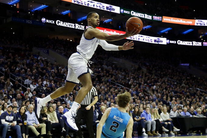 Villanova's Phil Booth, left, goes up for a shot over Georgetown's Mac McClung during the first half of an NCAA college basketball game, Sunday, Feb. 3, 2019, in Philadelphia. (AP Photo/Matt Slocum)