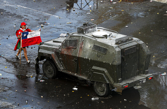 A demonstrator holds a Chilean flag toward an armored police vehicle during an anti-government march in Santiago, Chile, Tuesday, Oct. 22, 2019. Unrest began last week when a rise in subway fares led to student protests, but then spread nationwide, fueled by frustration among many Chileans who feel they have note shared in the economic advances in one of Latin America's wealthiest nations. (AP Photo/Esteban Felix)