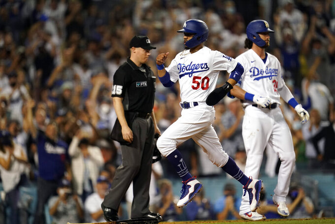Los Angeles Dodgers' Mookie Betts (50) scores on a single by Will Smith during the eighth inning of the team's baseball game against the Colorado Rockies on Saturday, Aug. 28, 2021, in Los Angeles. (AP Photo/Marcio Jose Sanchez)
