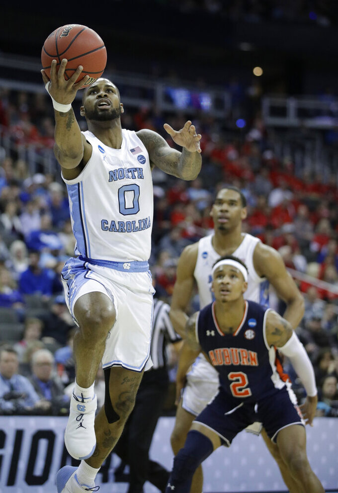 North Carolina's Seventh Woods (0) heads to the basket as Auburn's Bryce Brown (2) watches during the first half of a men's NCAA tournament college basketball Midwest Regional semifinal game Friday, March 29, 2019, in Kansas City, Mo. (AP Photo/Charlie Riedel)