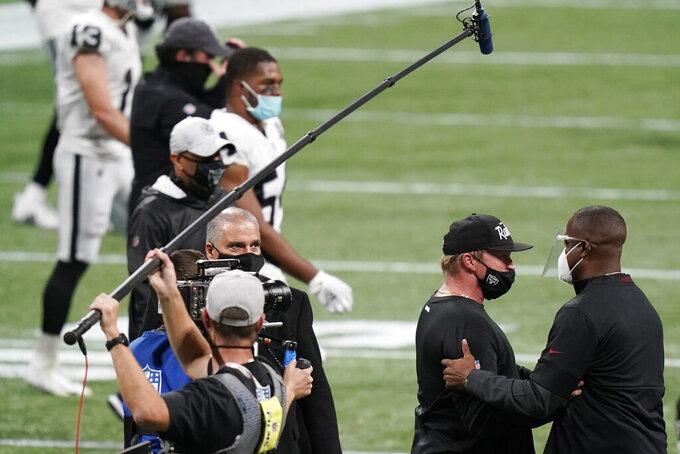 Atlanta Falcons interim head coach Raheem Morris, right, speaks with Las Vegas Raiders head coach Jon Gruden after an NFL football game, Sunday, Nov. 29, 2020, in Atlanta. The Atlanta Falcons won 43-6. (AP Photo/Brynn Anderson)