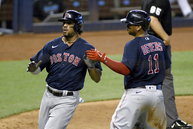 Boston Red Sox's Rafael Devers, right, and Xander Bogaerts celebrate after scoring during the sixth inning of a baseball game against the Miami Marlins, Thursday, Sept. 17, 2020, in Miami. (AP Photo/Gaston De Cardenas)