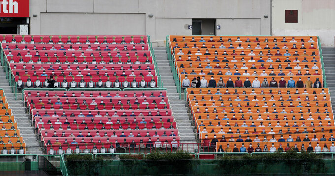 Spectators' seats are covered with pictures of fans before the start of a regular season baseball game between Hanwha Eagles and SK Wyverns in Incheon, South Korea, Tuesday, May 5, 2020. South Korea's professional baseball league start its new season on May 5, initially without fans, following a postponement over the coronavirus. (AP Photo/Lee Jin-man)